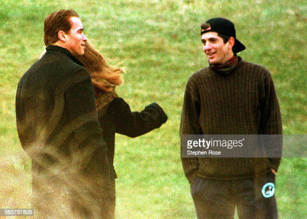 John F Kennedy Jr talks with actor Arnold Schwarzenegger at the Kennedy Compound in Hyannis Port Massachusetts while attending a wake for Rose...