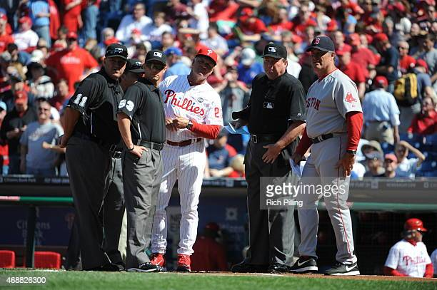John Farrell manager of the Boston Red Sox and Ryan Sandberg manager of the Philadelphia Phillies are seen going over the ground rules with the MLB...
