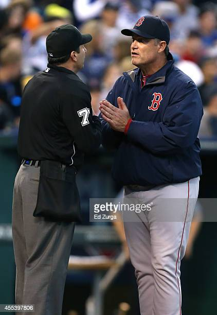 John Farrell manager of the Boston Red Sox talks with plate umpire Jim Reynolds after starting pitcher Rubby De La Rosa was charged with a balk that...