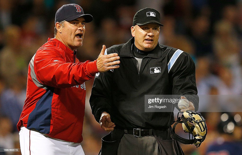 John Farrell #53 of the Boston Red Sox has words with umpire Jeff Nelson in the 8th inning over a call at first base against the Minnesota Twins at Fenway Park on May 7, 2013 in Boston, Massachusetts.