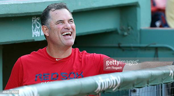 John Farrell of the Boston Red Sox laughs while he makes a visit to the dugout before a game against the Cleveland Indians at Fenway Park on August...