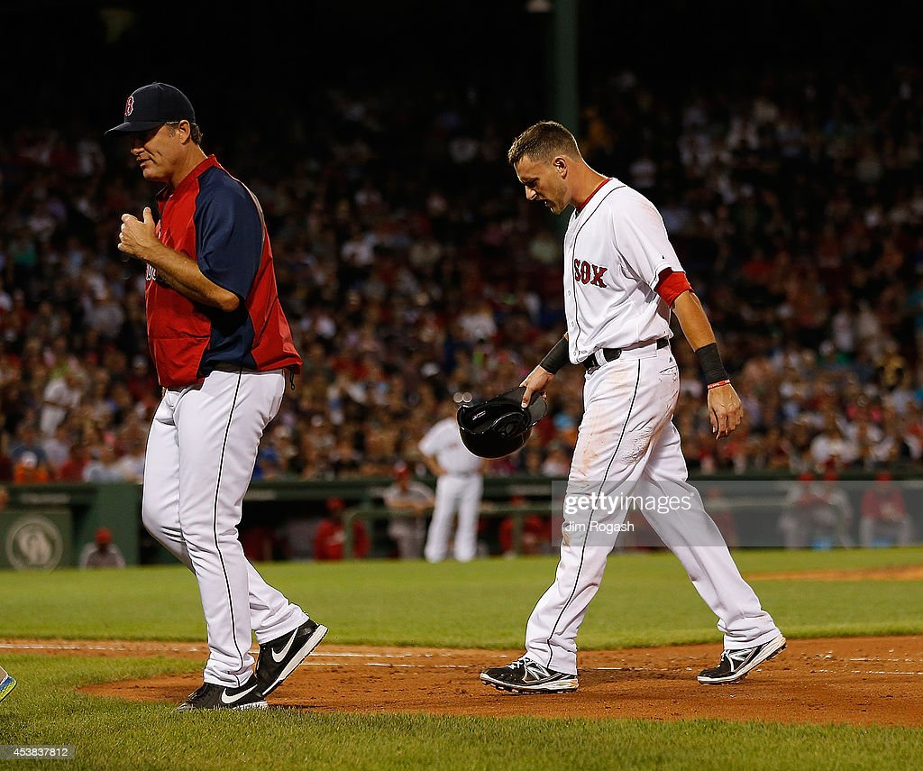 John Farrell #53 of the Boston Red Sox removes Will Middlebrooks #16 from the game because of an injury in the fourth inning against the Los Angeles Angels of Anaheim at Fenway Park on August 19, 2014 in Boston, Massachusetts.
