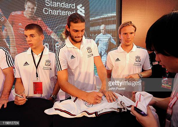 John Flanagan Andy Carroll and Christian Poulsen of Liverpool sign autographs during a visit to the Pavilion Mall in Kuala Lumpur as part of the...