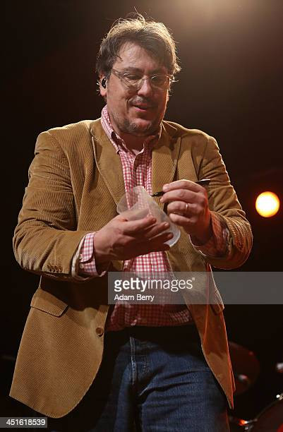 John Flansburgh of They Might Be Giants signs his autograph on a plastic beer glass during a concert at Astra on November 23 2013 in Berlin Germany