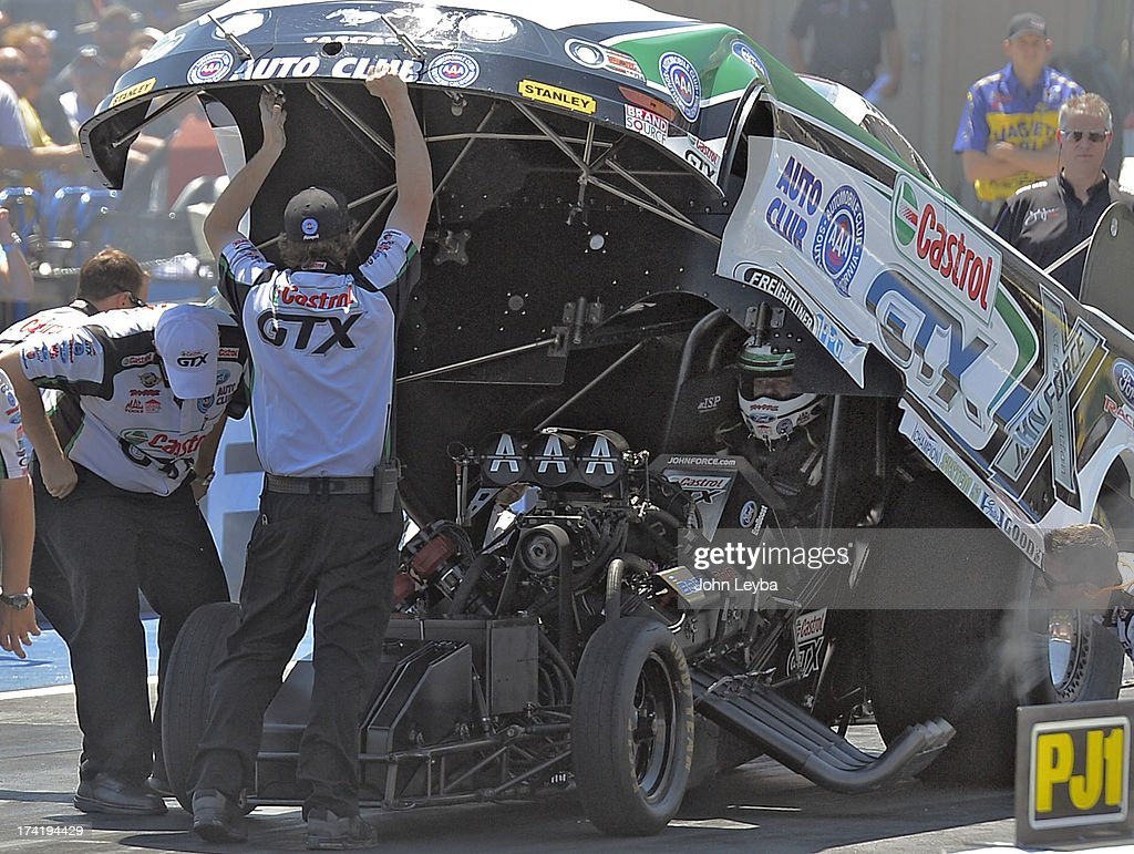 John Force sits in his car after his burnout as he prepares for his race with Bob Tasca III int he first round of the Mopar Mile-High NHRA Nationals July 21, 2013 at Bandimere speedway in Morrison.