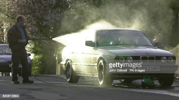 John Gardner of Brockley Park southeast London uses a power jet wash to clean his BMW car of graffiti after more than 60 cars on two estates were...