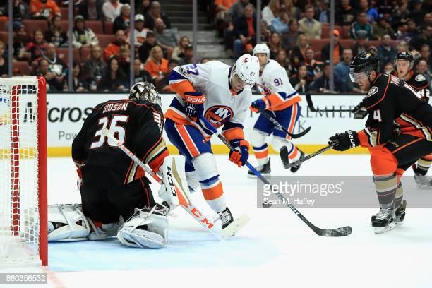 John Gibson and Cam Fowler of the Anaheim Ducks defend against Anders Lee of the New York Islanders during the second period of a game at Honda...