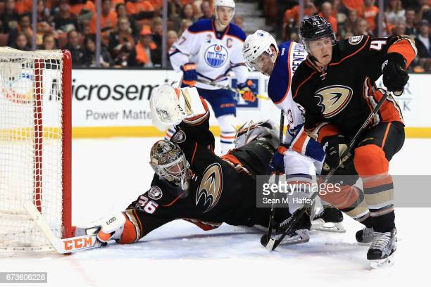 John Gibson and Josh Manson of the Anaheim Ducks defend against a shot on goal as Ryan NugentHopkins of the Edmonton Oilers pushes forward in the...