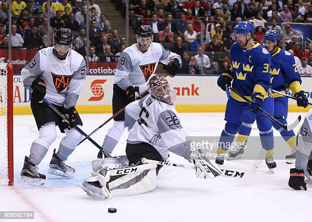 John Gibson of Team North America redirects the puck to the side of the net with Henrik Sedin of Team Sweden in front during the World Cup of Hockey...