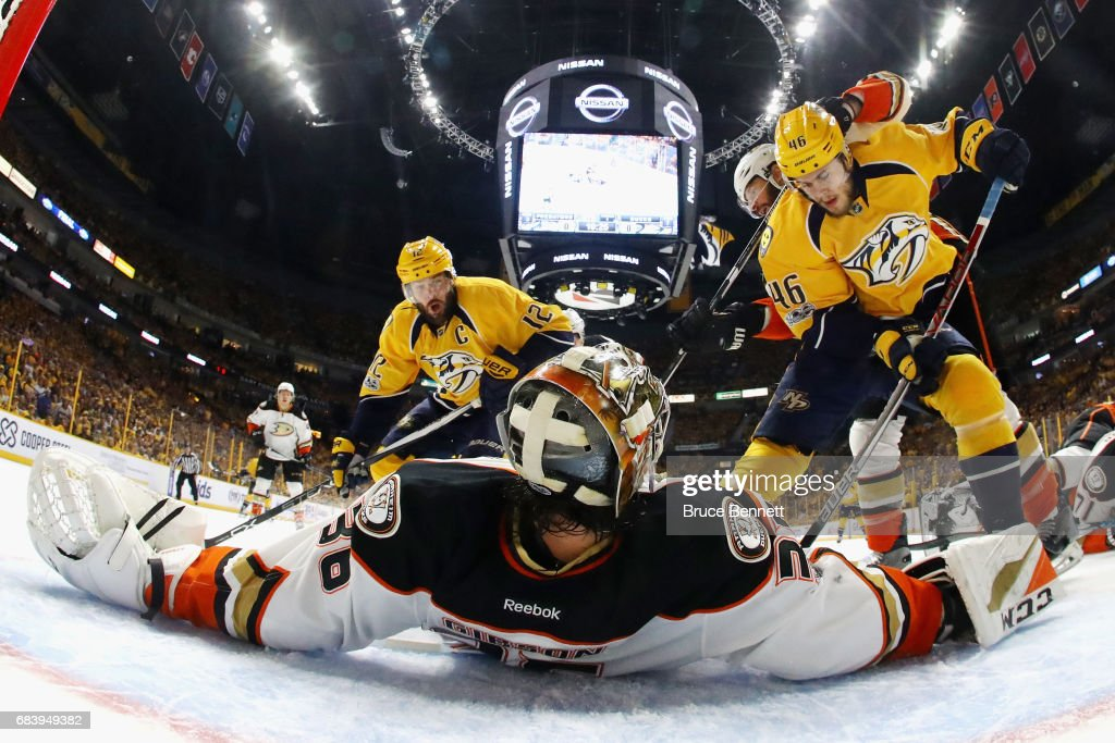 John Gibson #36 of the Anaheim Ducks lies on the ice as he makes a save against Pontus Aberg #46 and Mike Fisher #12 of the Nashville Predators during the first period in Game Three of the Western Conference Final during the 2017 Stanley Cup Playoffs at Bridgestone Arena on May 16, 2017 in Nashville, Tennessee.