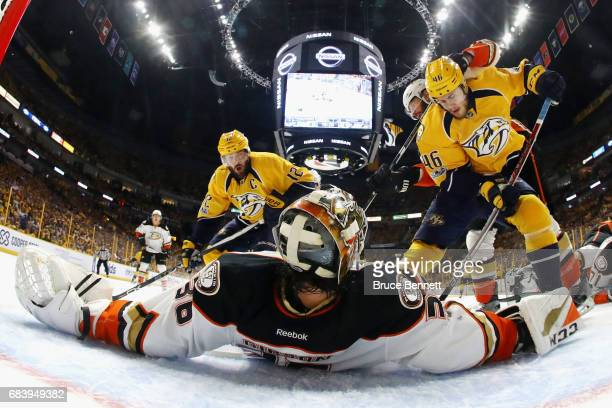 John Gibson of the Anaheim Ducks lies on the ice as he makes a save against Pontus Aberg and Mike Fisher of the Nashville Predators during the first...
