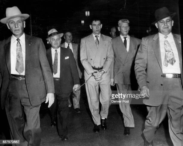 John Gilbert Graham's hand are shackled to a heavy belt as he is escorted to district court by a heavy guard of officials from the sheriff's office...