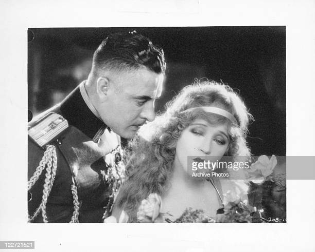 John Gilbert stands beside Lillian Gish as she kisses a rose in a scene from the film 'The Merry Widow' 1925