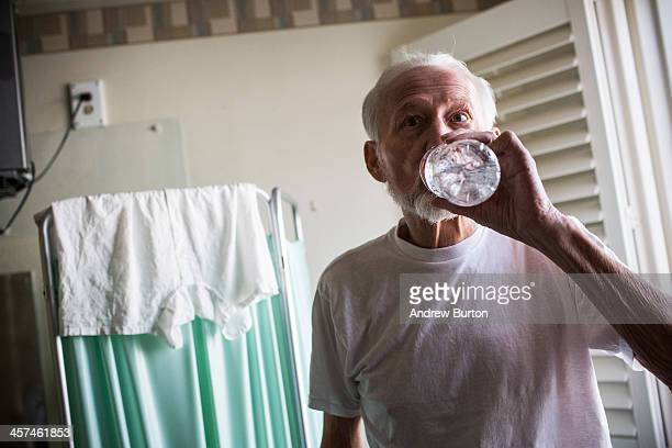 John Gillis age 73 a hospice care patient diagnosed with terminal colon cancer takes his daily medication in the hospice care wing of California...