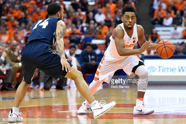John Gillon of the Syracuse Orange controls the ball as Dallas Moore of the North Florida Ospreys defends during the second half at the Carrier Dome...
