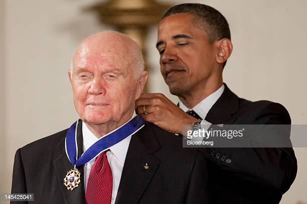 John Glenn former Marine Corps pilot astronaut and US Senator left receives the Presidential Medal of Freedom from US President Barack Obama at the...