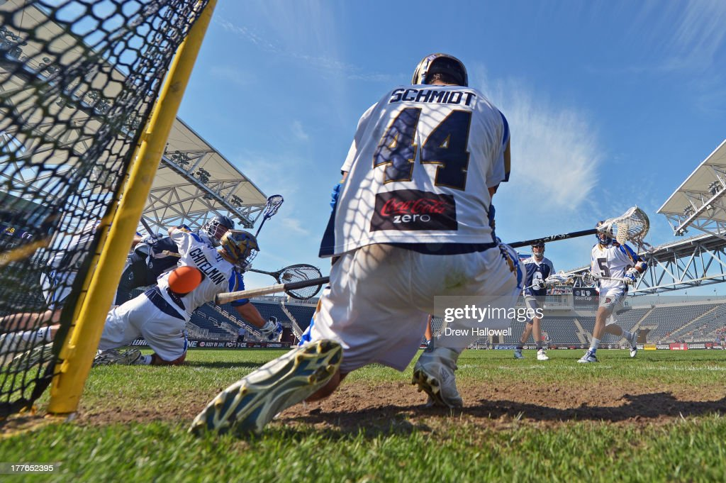 John Grant Jr #24 of the Chesapeake Bayhawks gets a shot past Adam Ghitelman and Brett Schmidt of the Charlotte Hounds during the MLL Championship at...