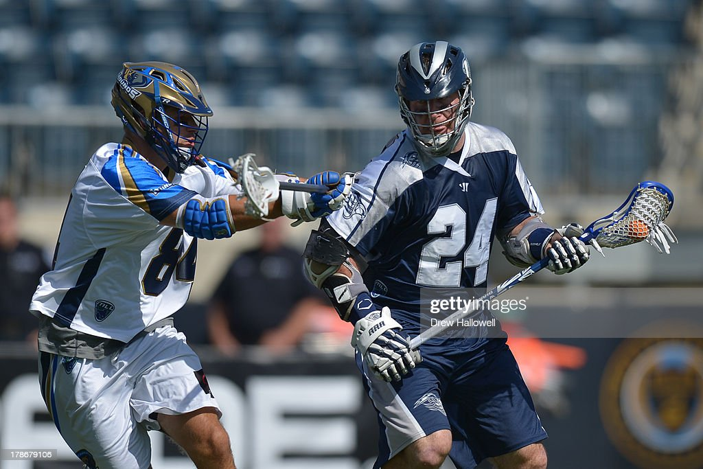 John Grant Jr. #24 of the Chesapeake Bayhawks is checked by Joe Cinosky #84 of the Charlotte Hounds during the MLL Championship at PPL Park on August 25, 2013 in Chester, Pennsylvania.