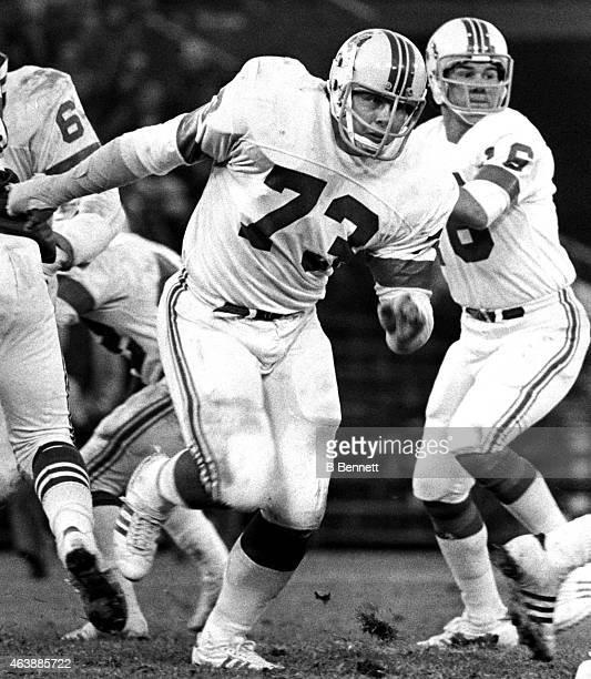 John Hannah of the New England Patriots runs on the field as quarterback Jim Plunkett looks to throw the ball during an NFL game circa 1973