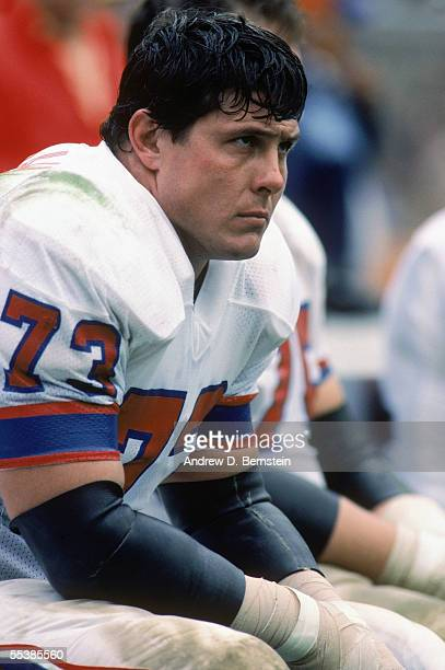 John Hannah of the New England Patriots sits on the sidelines during a game in December of 1983