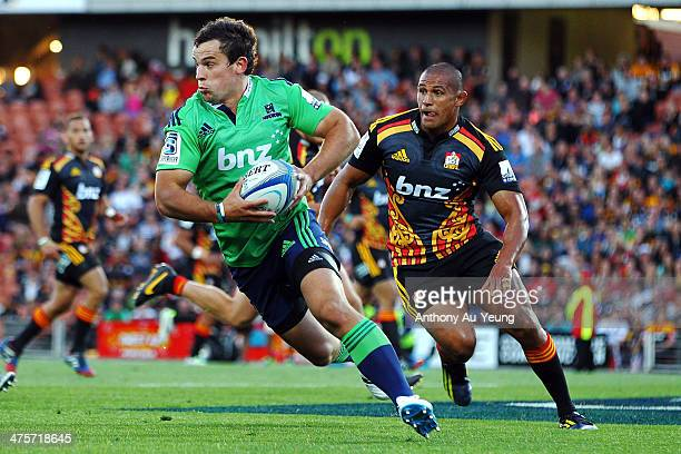 John Hardie of the Highlanders makes a run around Tanerau Latimer of the Chiefs during the round three Super Rugby match between the Chiefs and the...