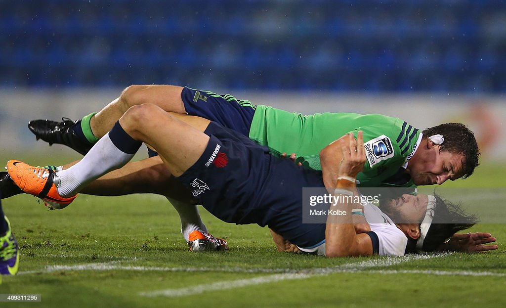 John Hardie of the Highlanders tackles Adam Ashley-Cooper of the Waratahs during the Super Rugby trial match between the Waratahs and the Highlanders at Hunter Stadium on February 14, 2014 in Newcastle, Australia.