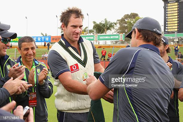 John Hastings of Australia is presented with the baggy green cap by former Australian cricketer Adam Gilchrist prior to the start of play on during...