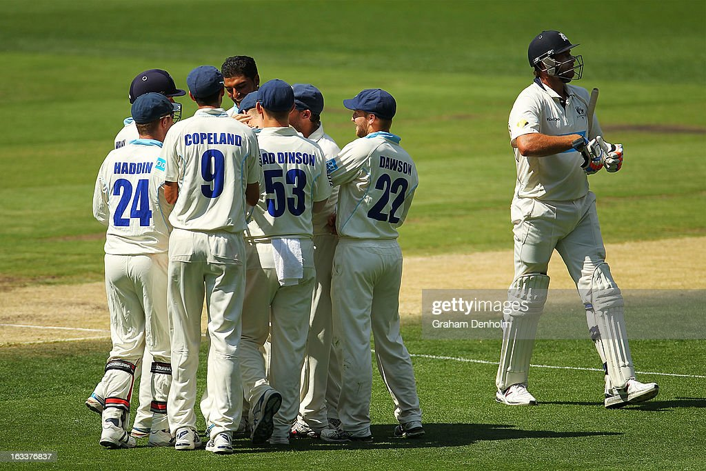 John Hastings of the Bushrangers (R) leaves the field looking dejected as the Blues celebrate his dismissal during day three of the Sheffield Shield match between the Victorian Bushrangers and the New South Wales Blues at Melbourne Cricket Ground on March 9, 2013 in Melbourne, Australia.