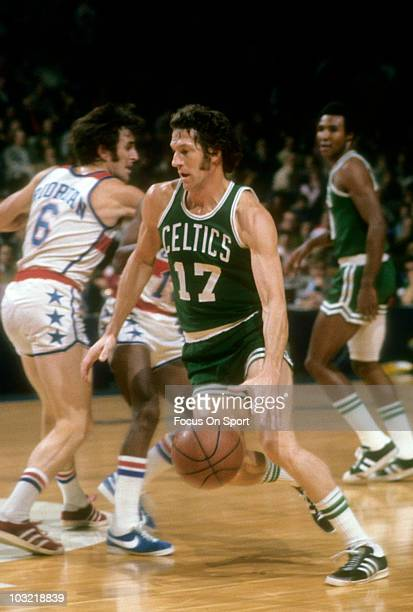 John Havlicek of the Boston Celtics dribbles around Mike Riordan of the Washington Bullets circa 1975 during an NBA basketball game at the Capital...