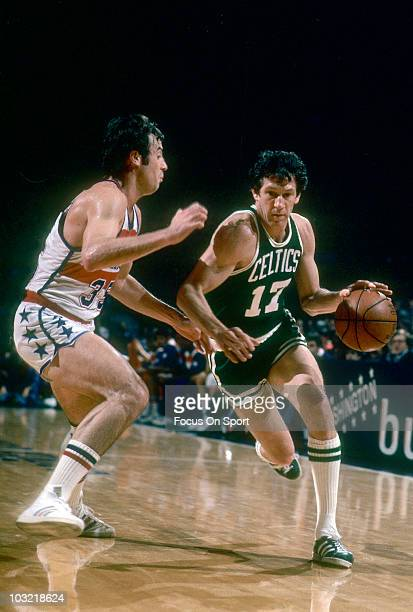 John Havlicek of the Boston Celtics dribbles the ball and is guarded closely by Kevin Grevey of the Washington Bullets circa 1975 during an NBA...