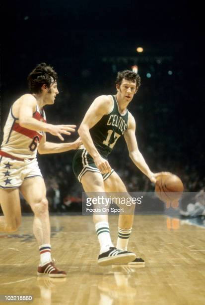 John Havlicek of the Boston Celtics dribbles the ball and is guarded closely by Mike Riordan of the Washington Bullets circa 1975 during an NBA...