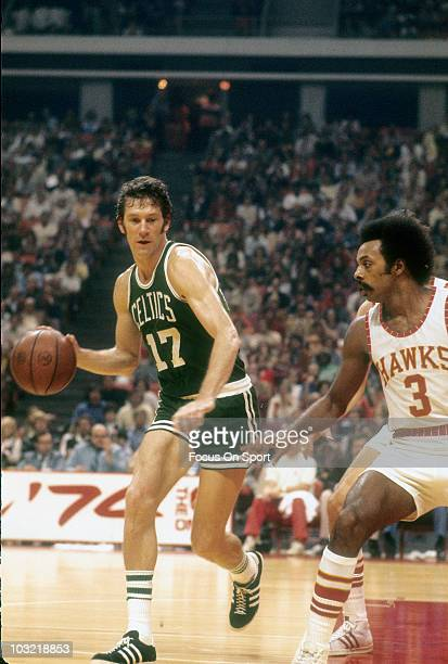 John Havlicek of the Boston Celtics dribbling the ball is guarded by Herm Gilliam of the Atlanta Hawks circa 1973 during an NBA basketball game at...