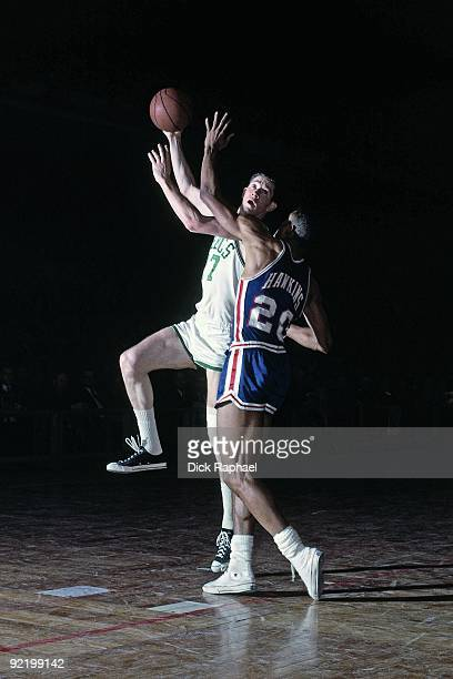 John Havlicek of the Boston Celtics goes up for a shot against Tom Hawkins of the Cincinnati Royals during a game played in 1965 at the Boston Garden...