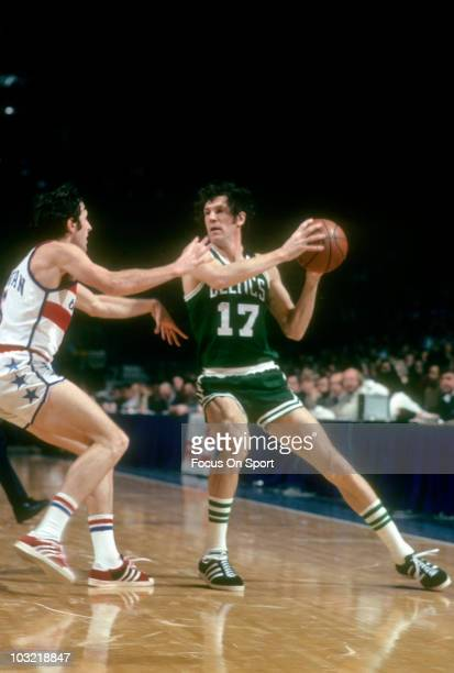 John Havlicek of the Boston Celtics keeps the ball away from defender Mike Riordan of the Washington Bullets circa 1975 during an NBA basketball game...