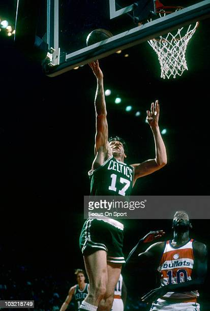 John Havlicek of the Boston Celtics lays the ball up in front of Bob Dandridge of the Washington Bullets circa 1977 during an NBA basketball game at...