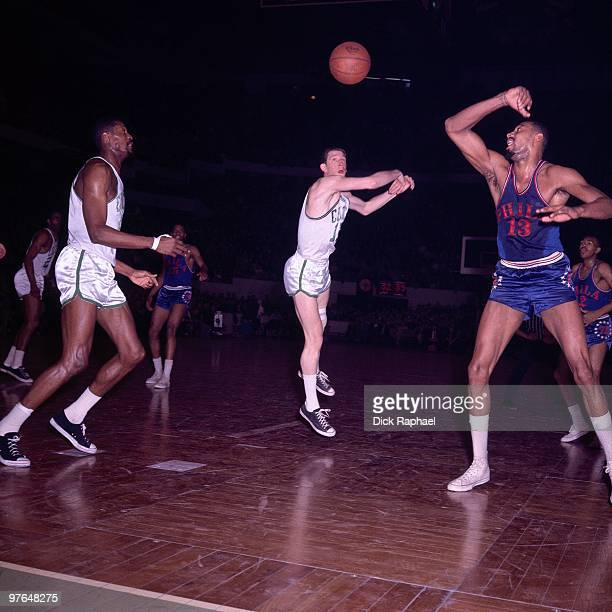 John Havlicek of the Boston Celtics passes against Wilt Chamberlain of the Philadelphia 76ers during a game played in 1965 at the Boston Garden in...