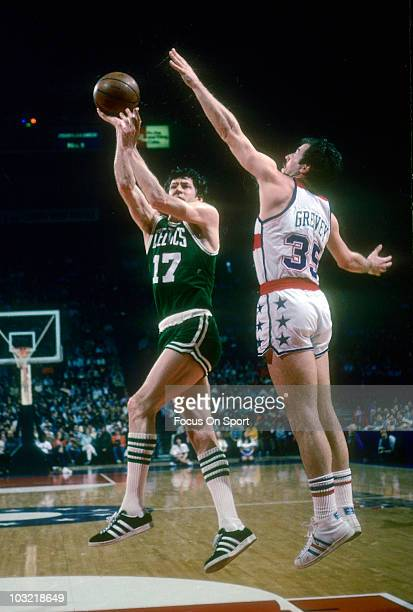 John Havlicek of the Boston Celtics shoots a hookshot over the out stretched arm of Kevin Grevey of the Washington Bullets circa 1975 during an NBA...