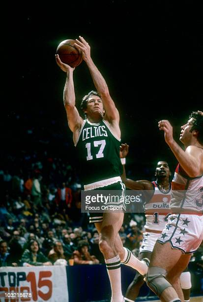 John Havlicek of the Boston Celtics shoots between Tom Henderson and Kevin Grevey of the Washington Bullets circa 1975 during an NBA basketball game...