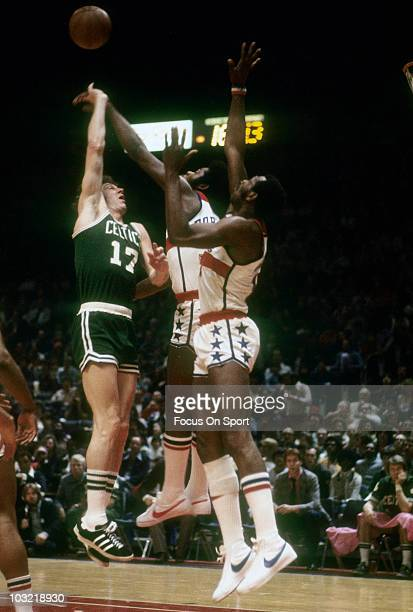 John Havlicek of the Boston Celtics tries to shoot over Bob Dandridge and Elvin Hayes of the Washington Bullets circa 1975 during an NBA basketball...
