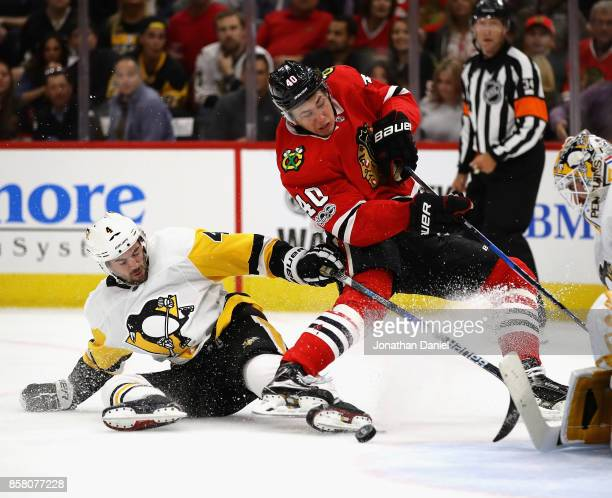 John Hayden of the Chicago Blackhawks is tripped while shooting by Justin Schultz of the Pittsburgh Penguins during the season opening game at the...