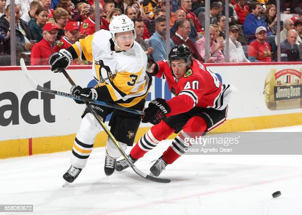 John Hayden of the Chicago Blackhawks reaches across Olli Maatta of the Pittsburgh Penguins in the second period at the United Center on October 5...