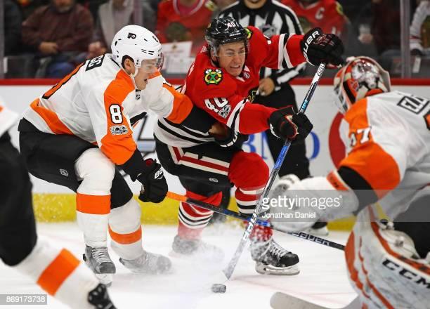 John Hayden of the Chicago Blackhawks shoots against Brian Elliott of the Philadelphia Flyers under pressure from Robert Hagg at the United Center on...