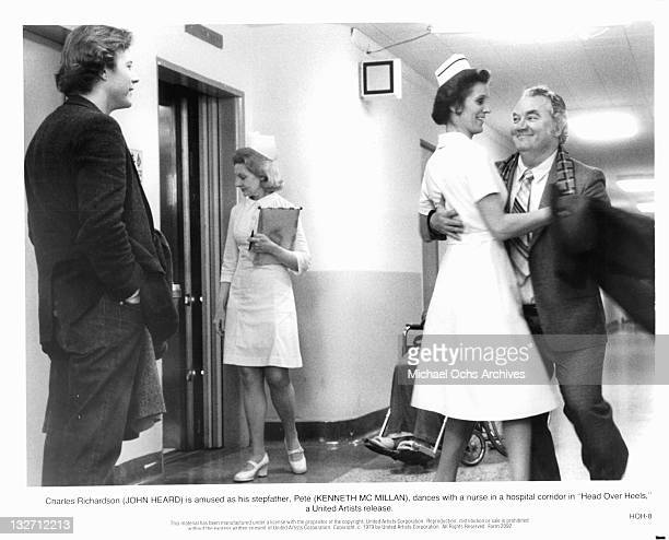 John Heard is amused as his stepfather Kenneth McMillan dances with a nurse in a scene from the film 'Head Over Heels' 1979