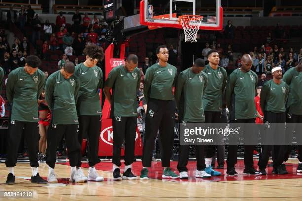 John Henson and Giannis Antetokounmpo of the Milwaukee Bucks with their teammates stand for the National Anthem before the preseason game against the...