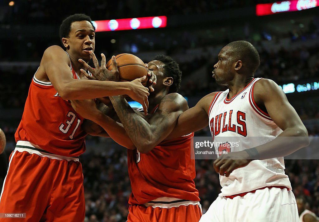 John Henson #31 and Larry Sanders #8 of the Milwaukee Bucks battle for a rebound with Loul Deng #9 of the Chicago Bulls at the United Center on January 9, 2013 in Chicago, Illinois. The Bucks defeated the Bulls 104-96.