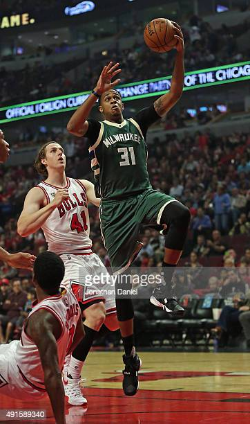 John Henson of the Milwaukee Bucks goes up for a shot past Cameron Bairstow of the Chicago Bulls during a preseason game at the United Center on...