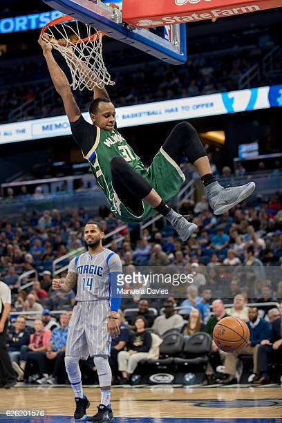 John Henson of the Milwaukee Bucks hangs on the basket after his dunk in the second half of the game against the Orlando Magic at Amway Center on...