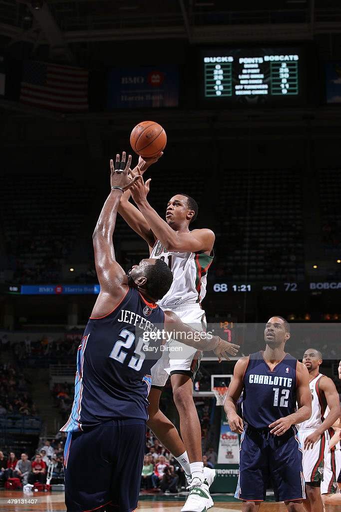 John Henson #31 of the Milwaukee Bucks shoots against Al Jefferson #25 of the Charlotte Bobcats on March 16, 2014 at the BMO Harris Bradley Center in Milwaukee, Wisconsin.