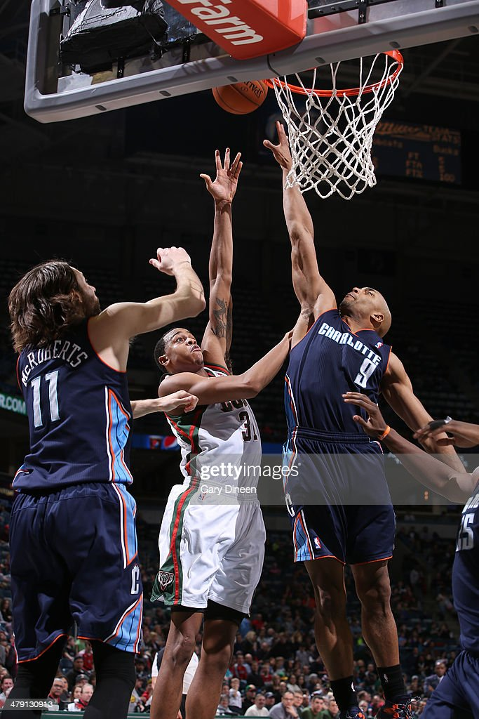 John Henson #31 of the Milwaukee Bucks shoots against (L-R) Josh McRoberts #11 and Gerald Henderson #9 of the Charlotte Bobcats on March 16, 2014 at the BMO Harris Bradley Center in Milwaukee, Wisconsin.