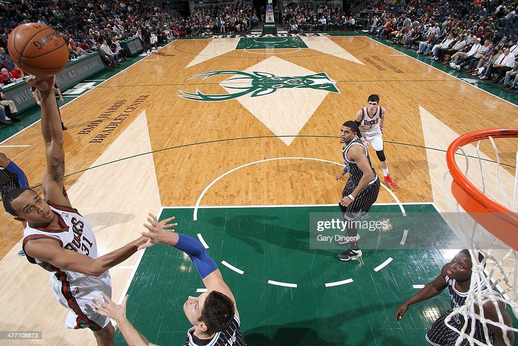 John Henson #31 of the Milwaukee Bucks shoots against Nikola Vucevic #9 of the Orlando Magic on March 10, 2014 at the BMO Harris Bradley Center in Milwaukee, Wisconsin.